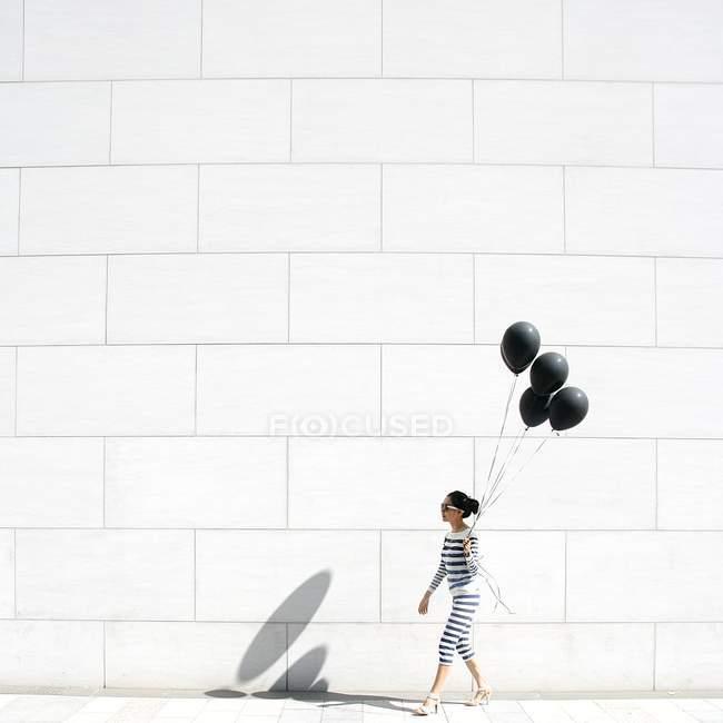 Frau zu Fuß mit schwarzen Luftballons — Stockfoto