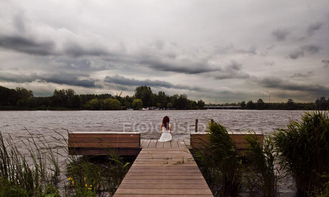 Woman sitting on jetty by lake in summer — Stock Photo