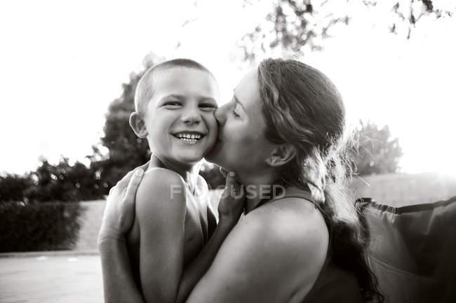 Мать целует сына в парке — стоковое фото