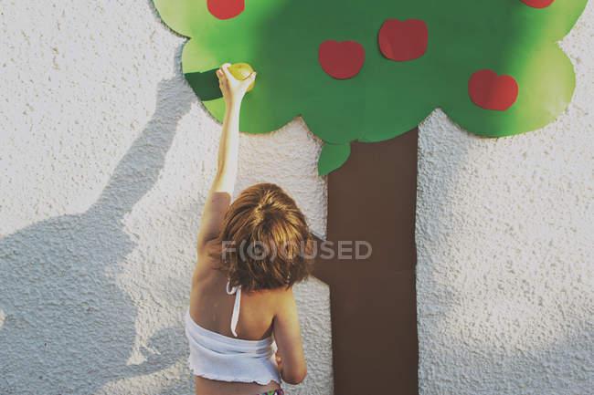 Girl pretending to be picking apple — Stock Photo