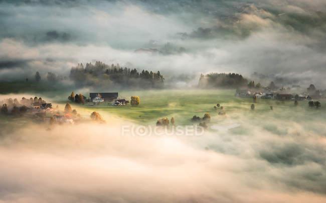 Manhã nevoeiro coberta pequena aldeia — Fotografia de Stock