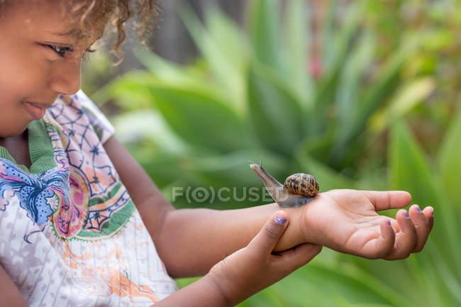Девушка с улиткой на руке — стоковое фото