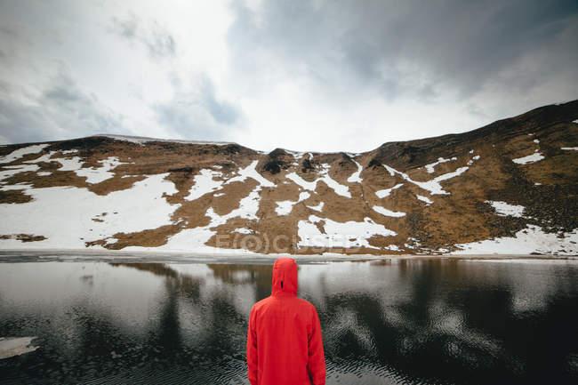 Homem olhando para lago de montanha — Fotografia de Stock