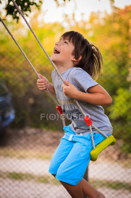 Boy laughing and swinging on a swing — Stock Photo
