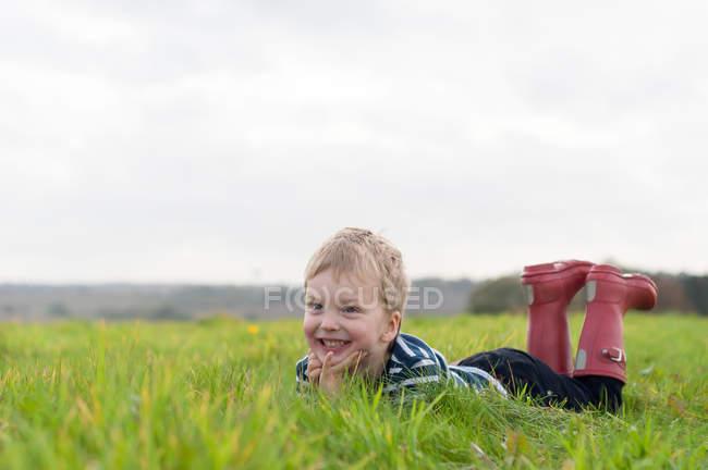 Мальчик лежит в траве — стоковое фото