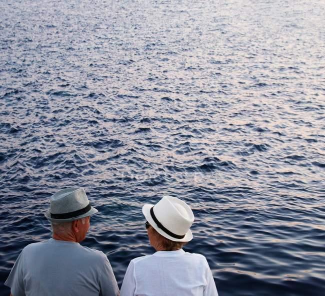 Paar mit Hüten schaut aufs Meer — Stockfoto