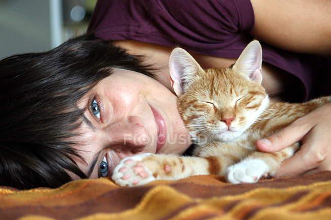 Mulher deitada na cama com gatinho — Fotografia de Stock
