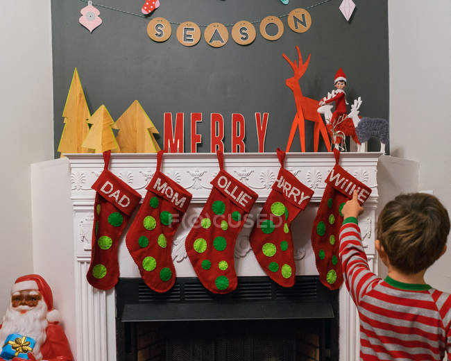 Boy pointing at christmas stockings — Stock Photo