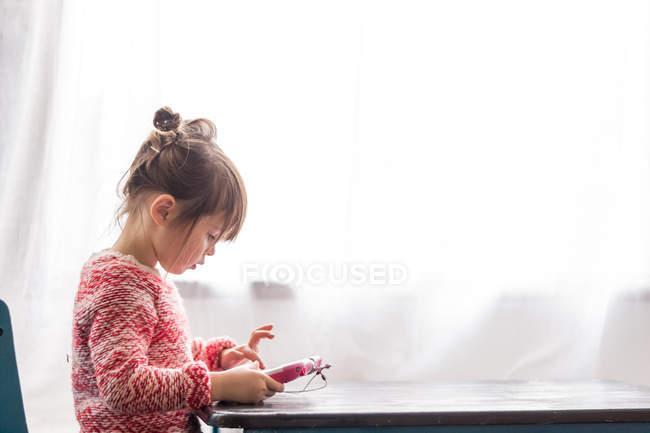 Chica jugando con la tableta digital - foto de stock