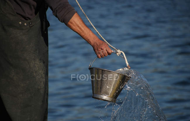 Fisherman holding bucket — Stock Photo