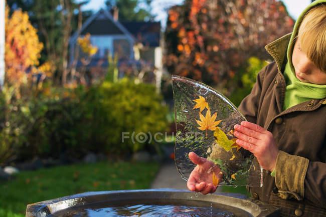 Junge draußen mit Blättern — Stockfoto