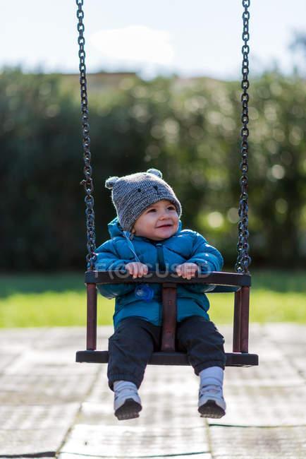 Menino sentado em um balanço — Fotografia de Stock