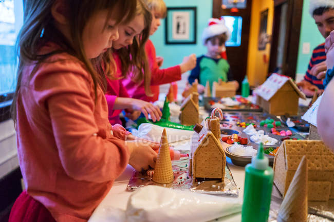 Children decorating gingerbread houses — Stock Photo