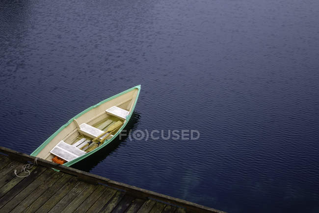 Rowing boat tied to a dock — Stock Photo