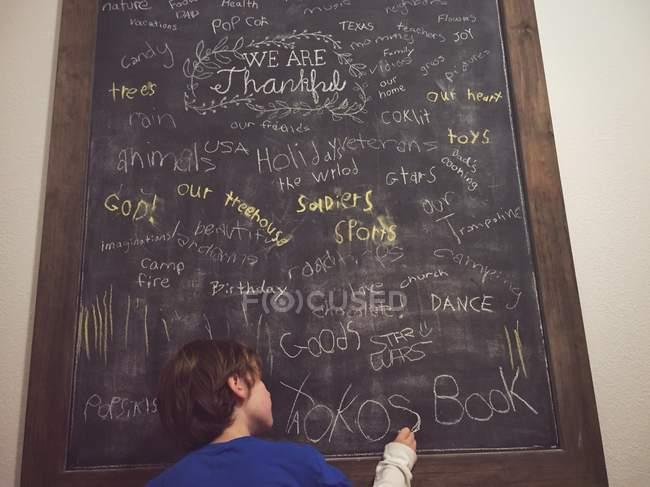 Menino escrevendo no quadro-negro — Fotografia de Stock