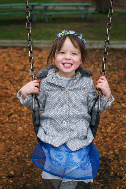 Sorrindo menina no balanço — Fotografia de Stock