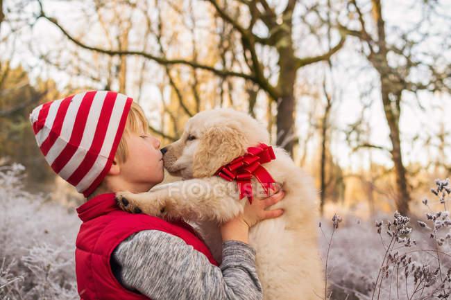 Boy kissing dog — Stock Photo