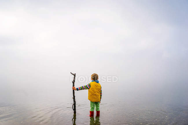 Boy holding stick and looking forward — Stock Photo