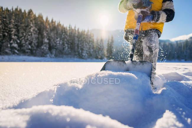 Junge schaufelt Schnee — Stockfoto