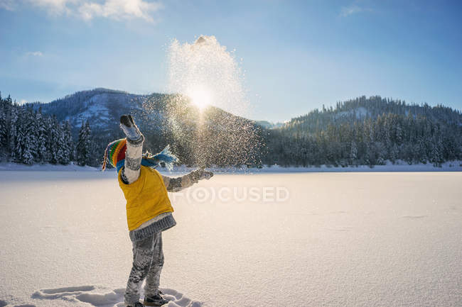 Boy throwing snow in air — Stock Photo