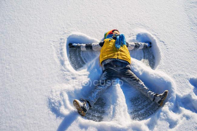 Ragazzo che fa un angelo di neve — Foto stock