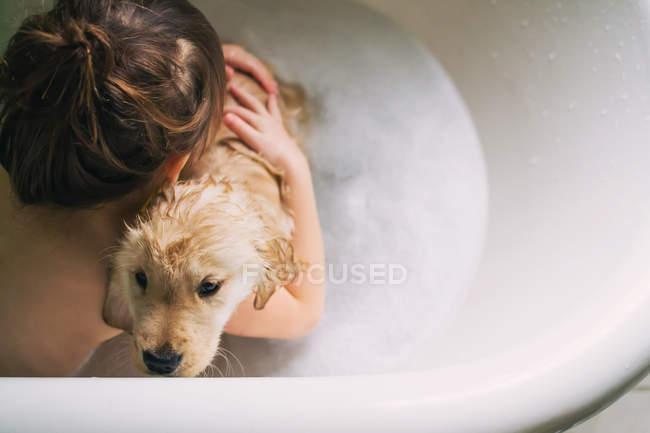 Boy taking bath with puppy dog — Stock Photo