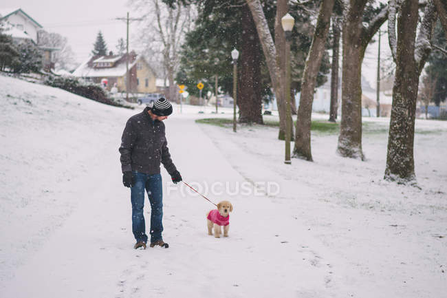Man walking with dog on snowy street — Stock Photo