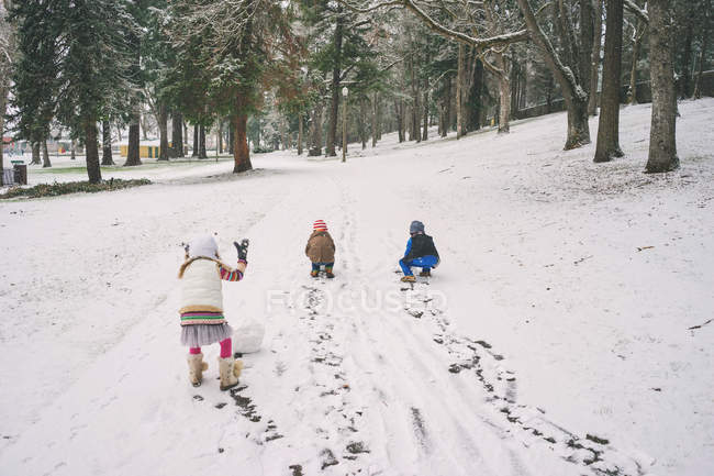 Boys and girl rolling snowballs — Stock Photo