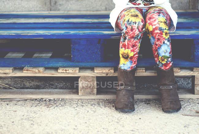 Girl sitting on wooden pallet — Stock Photo