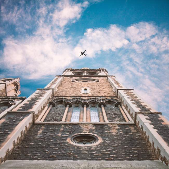 Torre da igreja com avião voando no céu acima — Fotografia de Stock