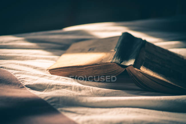 Buch im Bett aufschlagen — Stockfoto