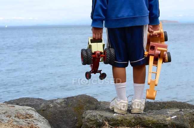 Boy with toys in both hands — Stock Photo