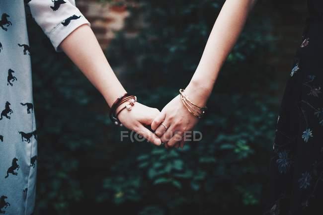 Dos chicas cogidos de la mano - foto de stock