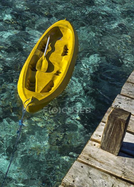 Canoa amarillo atado al muelle de madera - foto de stock