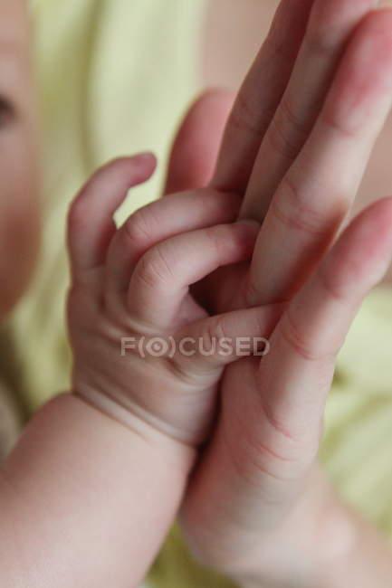 Madre de la mano de su bebé - foto de stock