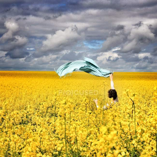 Woman standing in a rapeseed field — Stock Photo