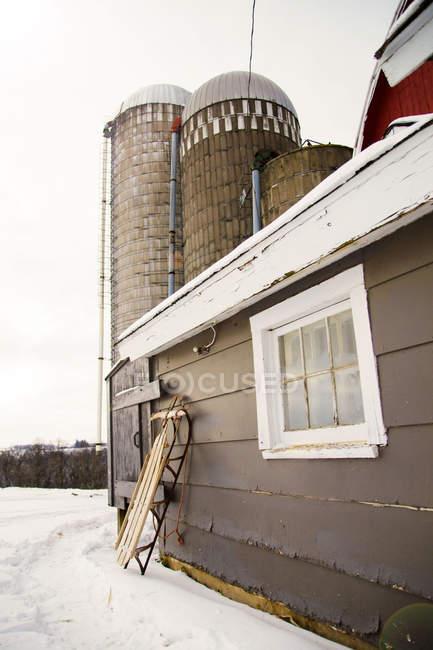 Slittino appoggiato a un edificio agricolo — Foto stock