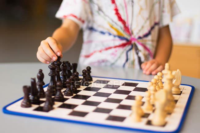 Мальчик играет в шахматы — стоковое фото