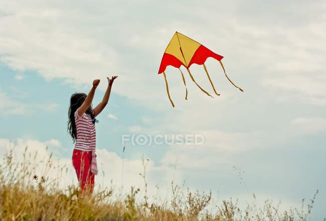 Menina com pipa voadora na colina — Fotografia de Stock