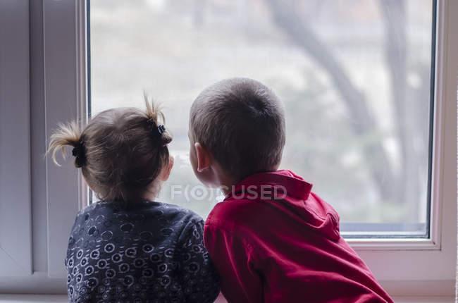 Хлопчика і дівчинки дивиться з вікна — стокове фото