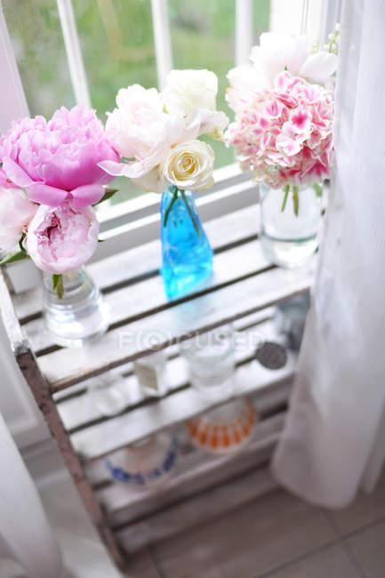 Flores em vasos de vidro, prateleira — Fotografia de Stock