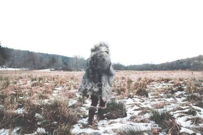 Donna a piedi attraverso prati innevati — Foto stock