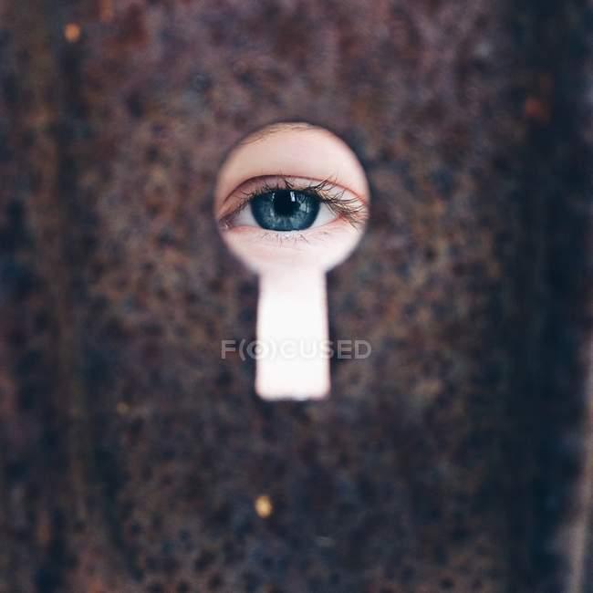 Девушка смотрит через замочную скважину — стоковое фото