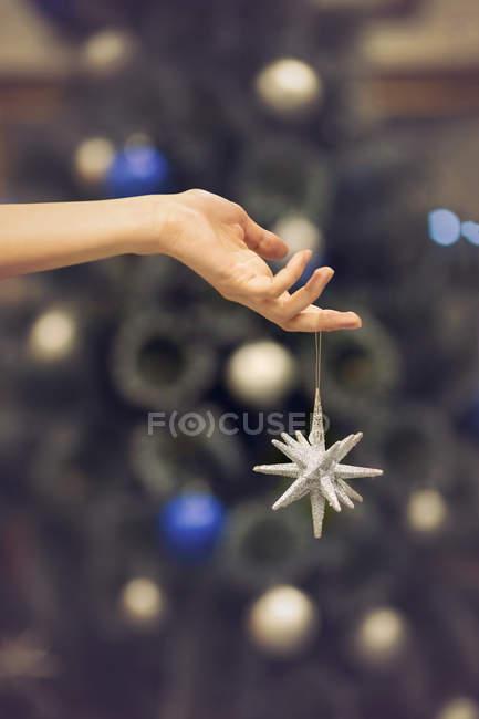 Mano que sostiene la estrella de Navidad plata - foto de stock