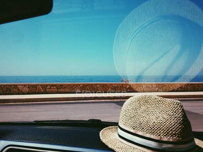 Chapéu de palha no painel do carro — Fotografia de Stock