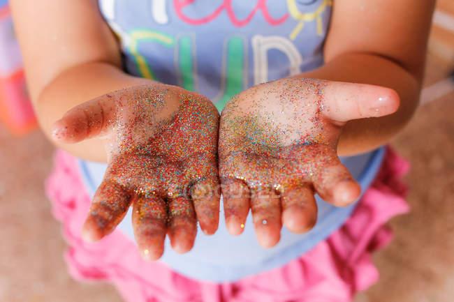 Glitter on girl hands — Stock Photo