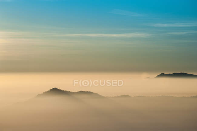 Горы в тумане на восходе солнца — стоковое фото