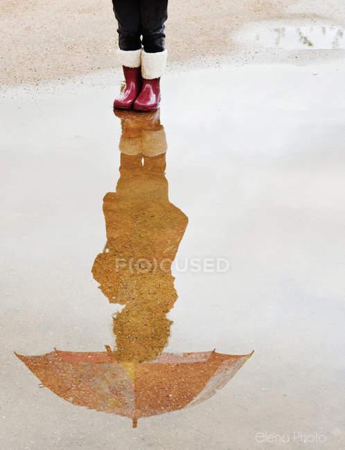 Menina, refletindo na poça — Fotografia de Stock