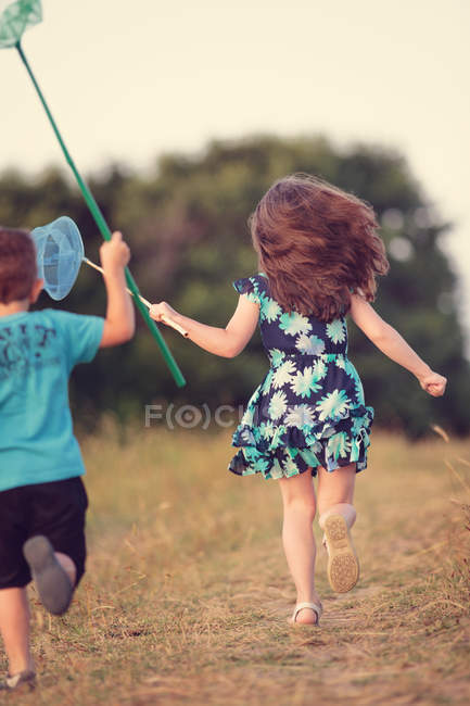 Boy and girl chasing butterflies — Stock Photo