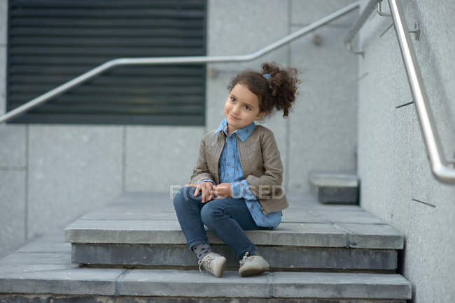 Smiling girl sitting on steps — Stock Photo